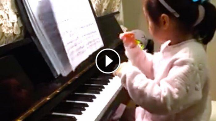 Ένα μικρό κορίτσι κάθεται σε ένα πιάνο φορώντας ροζ πιτζάμες. Παρακολουθήστε όταν αρχίζει να παίζει …